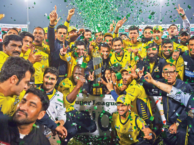 Jubilant Peshawar Zalmi players pose with the PSL trophy in Lahore. PHOTO: AFP