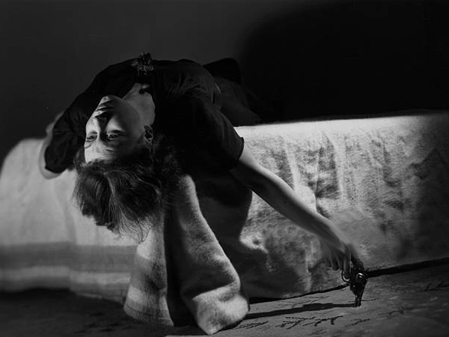 A woman sprawls over a bed holding a gun in her hand as she contemplates suicide. PHOTO: GETTY