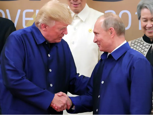 Donald Trump shakes hands with Russia's President Vladimir Putin as they pose for a group photo ahead of the Asia-Pacific Economic Cooperation Summit in Da Nang, Vietnam on Nov. 10, 2017. PHOTO: GETTY