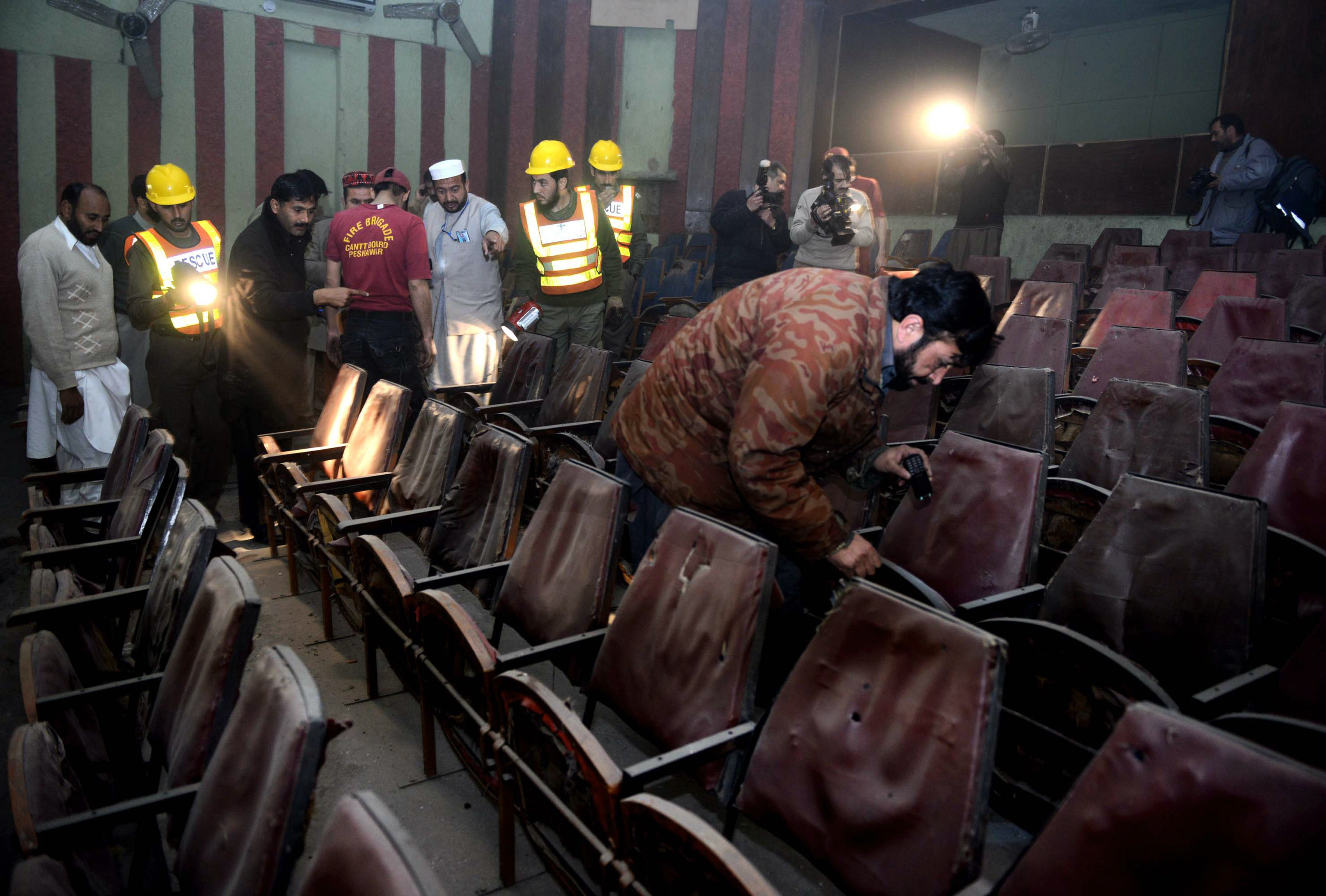 Volunteers and security officials investigate the cinema after the attack.  PHOTO: AFP