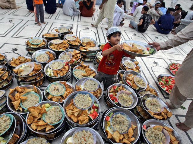 A Pakistani boy distributes plates of food donated to worshippers to break their fast, on the first day of the holy fasting month of Ramazan, in a mosque in Karachi. PHOTO: AP
