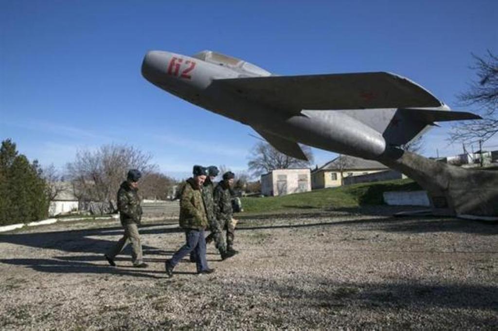 Ukrainian servicemen walk on the territory of a military unit located in the village of Lyubimovka near a local airfield southwest of Simferopol, Crimea's capital. PHOTO: REUTERS