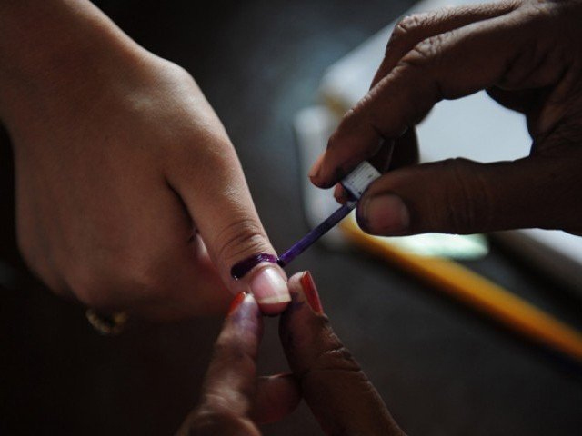 A Pakistani election presiding officer marks a voter's thumb with indelible ink during the re-poll of voters in the constituency known as NA-250 in Karachi on May 19, 2013. PHOTO: AFP