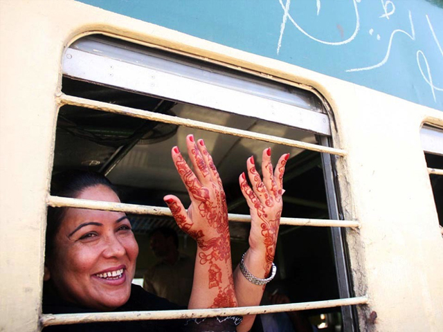 A woman showing Mehndi on her hands as she sits on first Eid Special Train leaving for Peshawar from Karachi's Cantt Railway Station in Pakistan. PHOTO: ONLINE