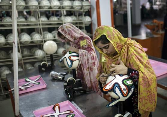 An employee adjusts outer panels on a soccer ball inside the soccer ball factory that produces official match balls for 2014 World Cup in Brazil, in Sialkot May 16, 2014. PHOTO: REUTERS