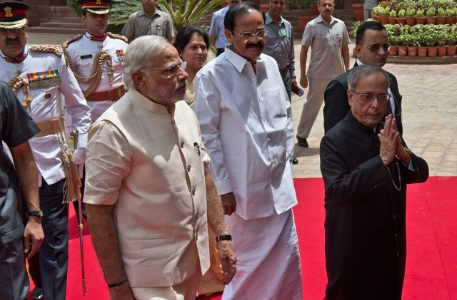 Indian President Pranab Mukherjee  gestures a greeting as he arrives with Indian Prime Minster Narendra Modi to address the joint session of Parliament in New Delhi. PHOTO: AFP