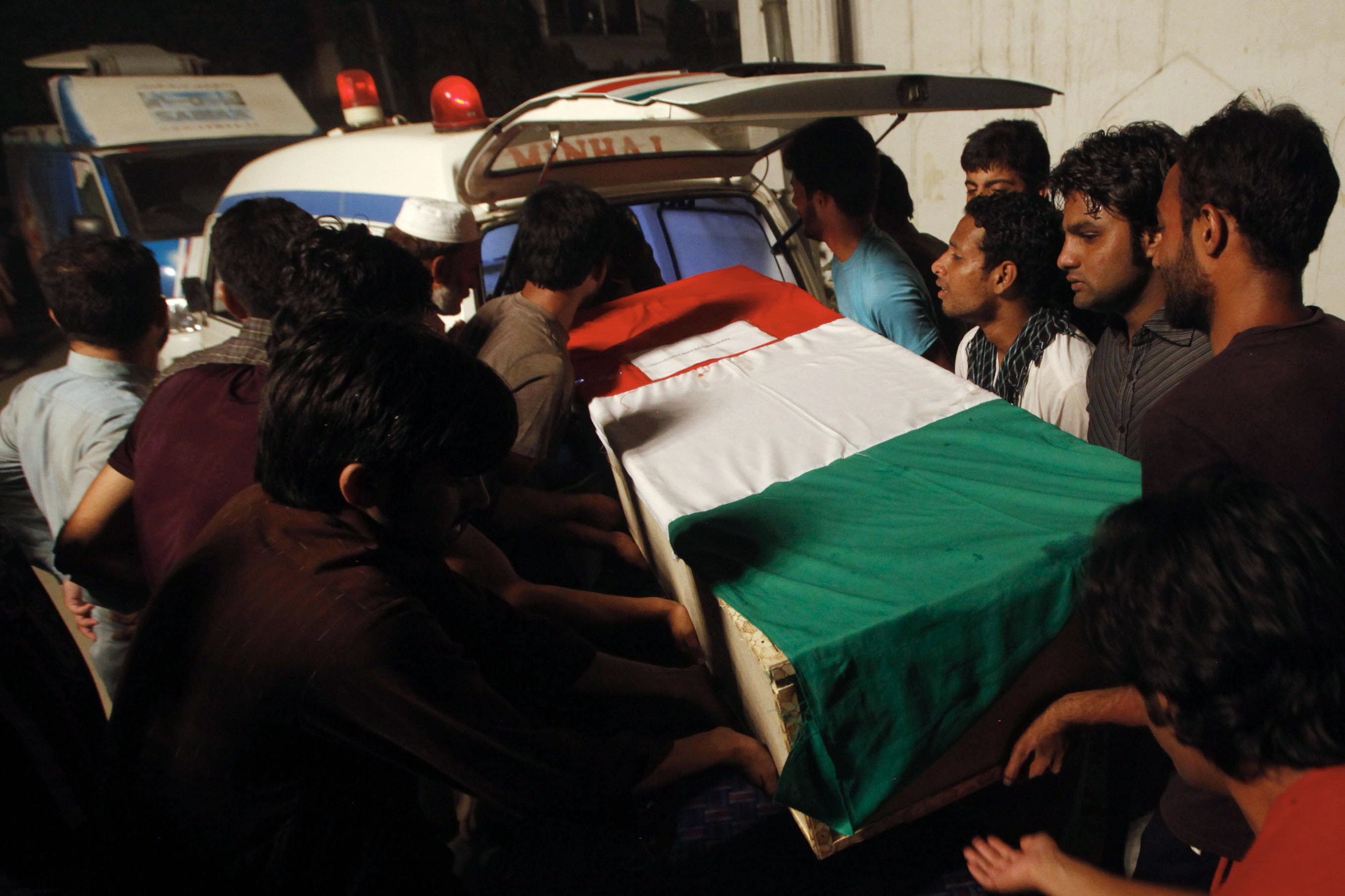 A coffin bearing a slain supporter of Tahirul-Qadri, killed during clashes with police, is shifted into an ambulance during a funeral ceremony in Lahore. PHOTO: AFP