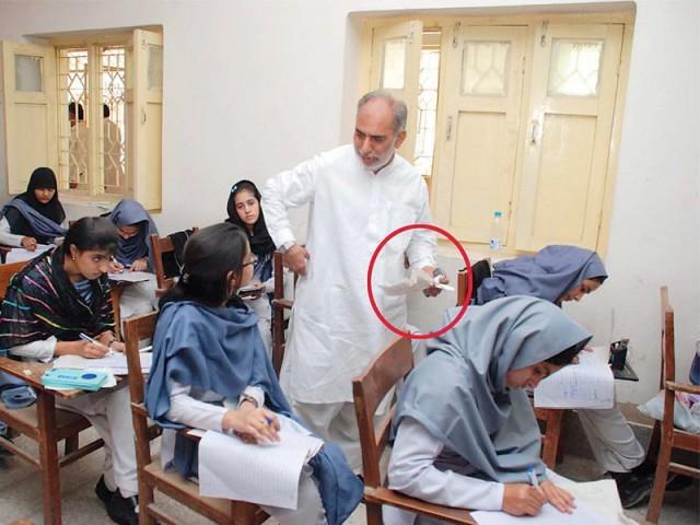 Board of Education, Sukkur, examination controller Mehmoodul Hasan Khokar confiscates cheating material from students. PHOTO: NAEEM AHMED GHOURI/EXPRESS