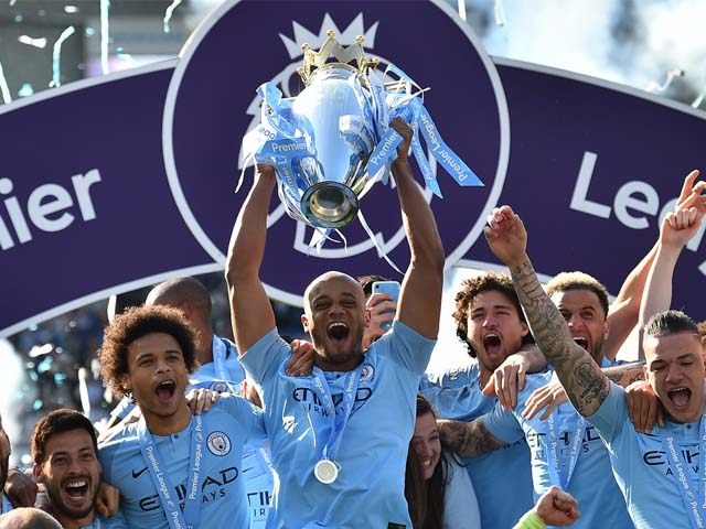 Manchester City's Belgian defender Vincent Kompany (C) holds up the Premier League trophy after their 4-1 victory in the English Premier League. PHOTO: AFP