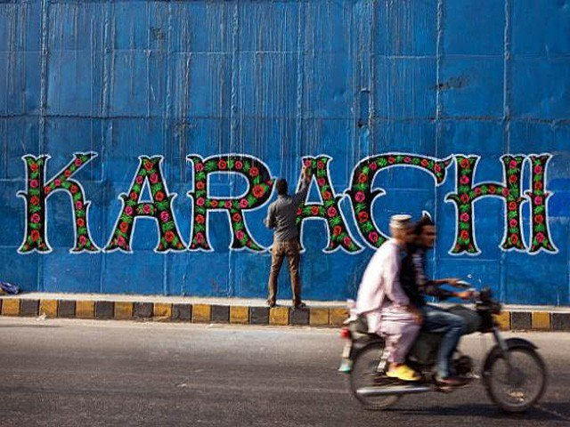 A street artist applies the final touches to a mural, part of the 'I am Karachi' campaign, as a motorcycle passes by in Karachi. PHOTO: GETTY