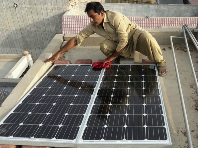 A man wipes the dust off solar panels he recently installed on the roof of his home in Larkana, in Pakistan's Sindh province, June 28, 2017. PHOTO: REUTERS