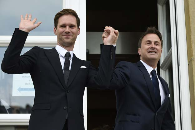 Luxembourg Prime Minister Xavier Bettel (R) holds hands with his companion Belgian architect Gauthier Destenay during their wedding in Luxembourg on May 15, 2015. PHOTO: AFP