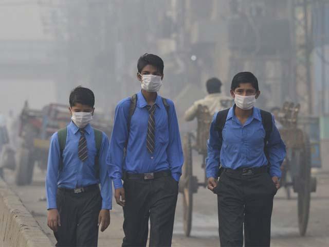 Pakistani school students return home as heavy smog envelops Lahore. PHOTO: GETTY