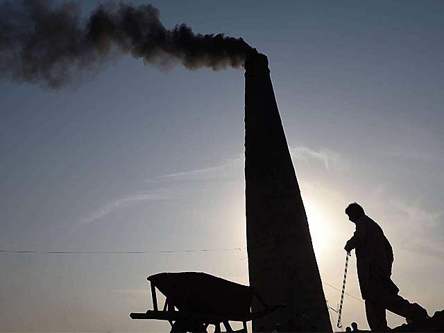 Smoke billows from a chimney as a Pakistani labourer works beside a brick kiln. PHOTO: GETTY