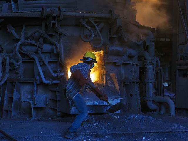 An employee shovels coal into a furnace used for smelting iron inside a steel plant in Karachi. PHOTO: GETTY