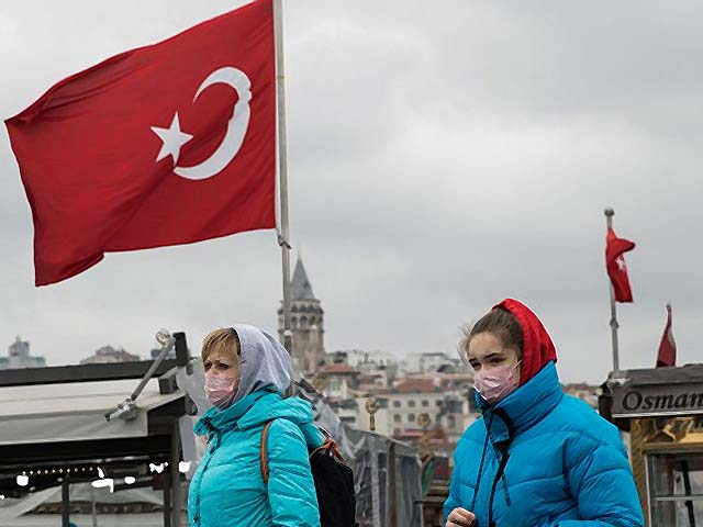 Tourists wearing protective face masks walk across Eminonu Square in Istanbul. PHOTO: GETTY