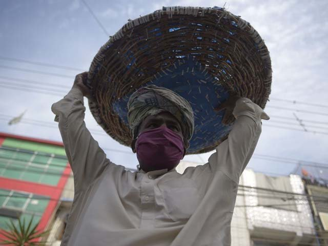 A labourer wearing a face mask carries his basket as he searches for customers. PHOTO: AFP