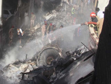 Rescue workers gather at the site after a PIA plane crashed. PHOTO: AFP