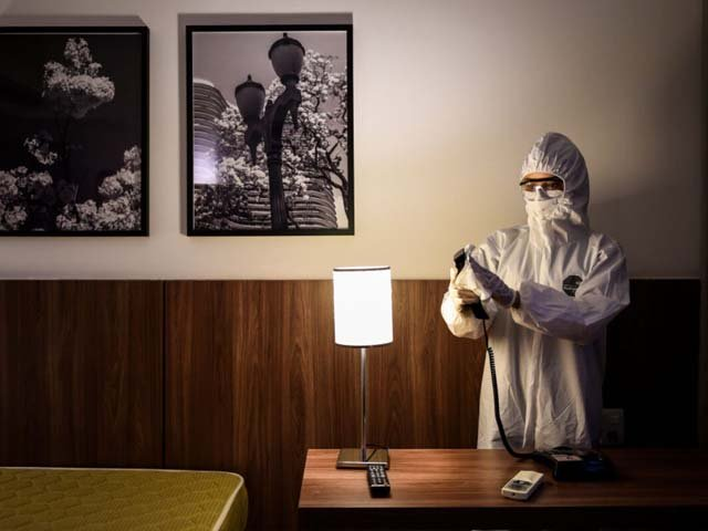 A member of the cleaning team disinfects a room at a hotel. PHOTO: AFP