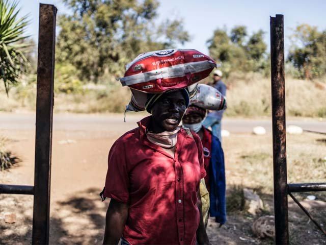 Residents of an informal settlement in Pretoria, leave with bags of food following a food distribution drive. PHOTO: AFP