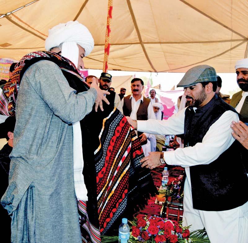 Dr Malik Baloch is presented a shawl by his adviser on finance Mir Khalid Langau. PHOTO: BANARAS KHAN/EXPRESS