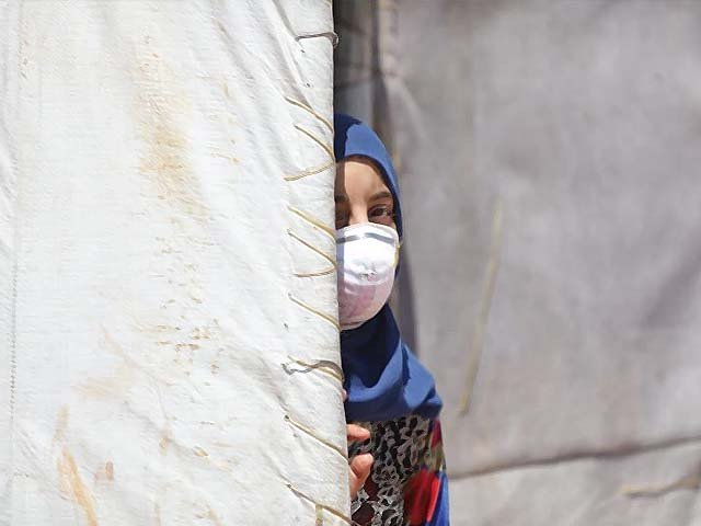 A Syrian girl wearing a medical mask is seen at a refugee camp where thousands of displaced Syrians shelter. PHOTO: AFP