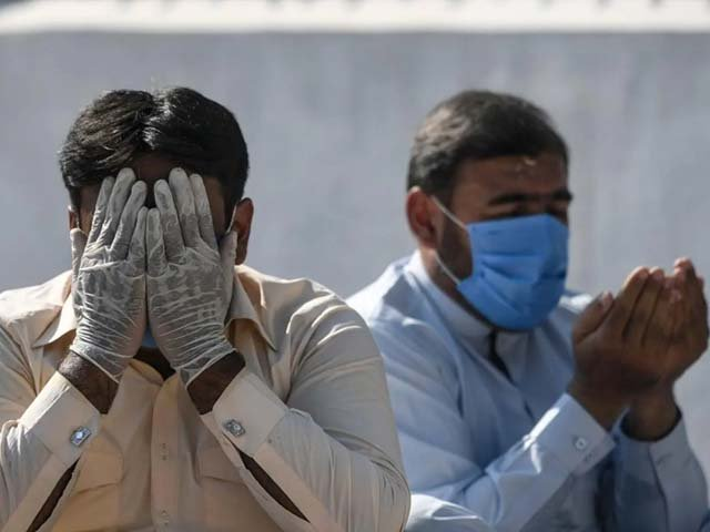 A man wearing a facemask and hand gloves offers prayers in Rawalpindi. PHOTO: AFP