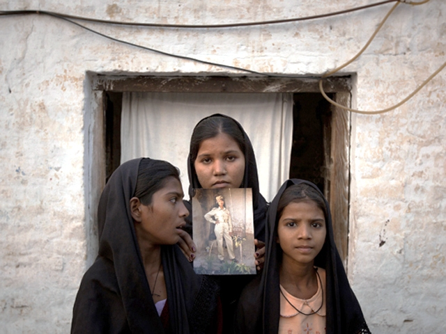 The daughters of Asia Bibi with an image of their mother, standing outside their residence in Sheikhupura on November 13, 2010. PHOTO: REUTERS