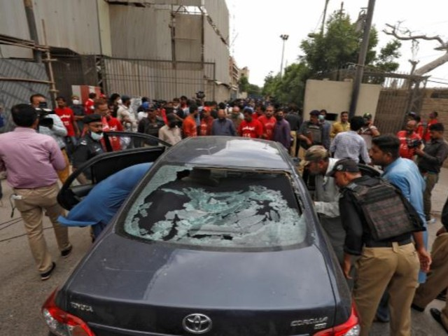 Police officers inspect the damaged car at the site of the attack at the Pakistan Stock Exchange entrance in Karachi. PHOTO: REUTERS
