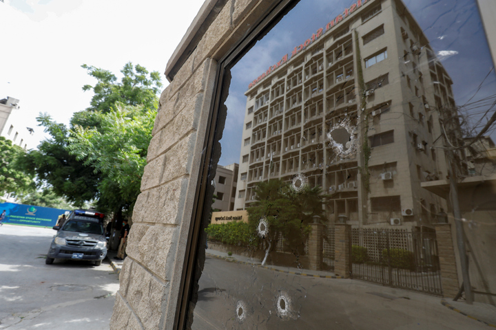 Aftermath: Bullet holes pepper the window of a security booth at the Pakistan Stock Exchange after it was attacked by terrorists on Monday, creating fear and panic in the city's financial centre. PHOTO: REUTERS